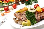 Grelhado de carne bife num prato branco sobre fundo branco isolado — Foto Stock