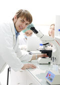 Science team working with microscopes in a laboratory, young researcher smi — Stockfoto