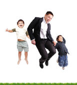 Father and sons jumping over green grass, isolated — Stock Photo
