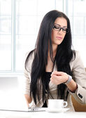 Office portrait of beautiful young business woman looking at her watch in o — Stock Photo