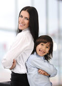 Young mother and son standing together, back to back indoor — Stock Photo