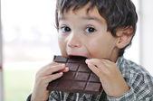 Lilla söta unge äta choklad — Stockfoto