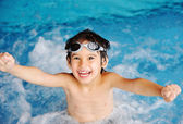 Little cute boy in blue water of the swimming pool, summer time for fun — Foto Stock