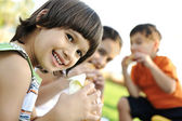 Small group of children in nature eating snacks together, sandwiches, bread — Stok fotoğraf