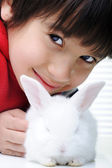 Happy child with beautiful cute Easter bunny pet — Stock Photo