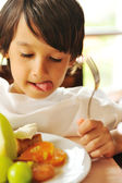 Real enjoying food, cute kid with finger in his mouth — Stock Photo