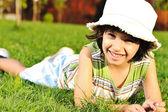 Dziecko z kapelusz na głowę na trawie w parku — Zdjęcie stockowe