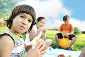 Happy group of children outdoor on meadow: eating and playing together — Stock Photo