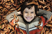 Little happy positive kid laying on fall ground, yellow and red leaves arou — Stock Photo