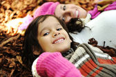 Little happy positive kid laying on fall ground with his mother, yellow and — Stock Photo