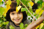 Happy childhood outdoor, happy faces between the leaves of the trees in for — Stock fotografie