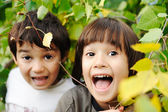 Happy childhood outdoor, happy faces between the leaves of the trees in for — Photo