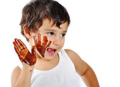 Cute messy kid isolated on white eating chocolate — Stock Photo