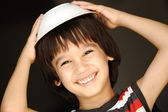 Cute kid with dish on head smiling — Stock Photo