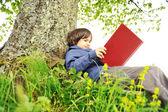 Happy children reading the book under the tree — Stock Photo
