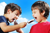 Two kids feeding each other ice cream — Stok fotoğraf
