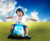 Happy kid on green meadow driving a car — Stock Photo