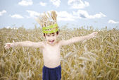 Cute kid in wheat meadow with wheat crown on head — Stock Photo