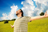 Happy succesful man in nature with wide open arms — Stock Photo