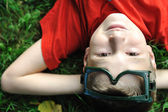 Cute positive boy with glasses laying on green grass ground and looking up — Stock Photo