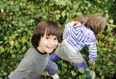 Happy childhood outdoor, happy faces between the leaves of the trees in for — Stockfoto