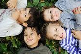 Caras felices, al aire libre entre las hojas de los árboles en el bosque o parque — Foto de Stock