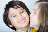 Adorable toddler girl kissing her brother — Stock Photo