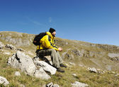 Man sitting on top of mountain — Foto de Stock