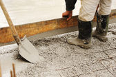 Man leveling concrete slab — Stockfoto