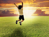 Happy child jumping on a green meadow — Stock Photo