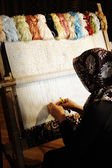 Woman working at the loom. Oriental Muslim national crafts. Focus on the fa — Stockfoto