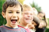 Foto de niñas felices con apuestos jóvenes sonrientes frente a cámara — Foto de Stock