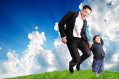 Father and son jumping outdoor on green meadow — Stock Photo