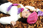 Close-up portrait of an beautiful autumn woman laying on ground — Stock Photo