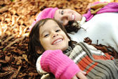 Close-up portrait of an beautiful autumn woman and kid laying on ground — Stock fotografie
