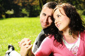 Young couple in love: lovers in park holding each other's hands and sm — Stock Photo