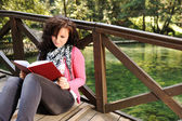 Young beautiful girl student sitting on wooden bridge over the bridge in n — Stock Photo