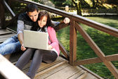Young couple, male and female sitting in park and studing and workind toget — ストック写真