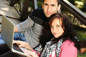 Young couple, male and female sitting in park and studing and workind toget — Stok fotoğraf