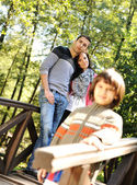 Beautiful scene of young happy family in natural park, three members: mothe — Stockfoto