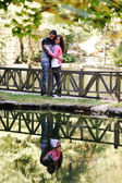 Young couple loving each other on river in nature with reflection in water — Stock Photo