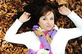 Young beauty girl laying on autumn ground and leaves, perfect face and natu — Foto de Stock