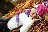 Young beauty girl laying on autumn ground and leaves, perfect face and natu — Zdjęcie stockowe