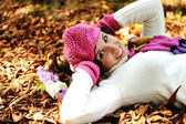 Young beauty girl laying on autumn ground and leaves, perfect face and natu — Stok fotoğraf