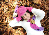 Young beauty girl laying on autumn ground and leaves, perfect face and natu — ストック写真
