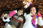 Little happy positive kid laying on fall ground with his mother, yellow and — Foto de Stock