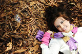 Young beauty girl laying on autumn ground and leaves, perfect face and natu — Stock fotografie