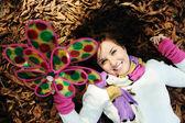 молодая красавица девушка кладки, улыбаясь и играя на осенний основании — Стоковое фото