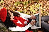 Schönheit wunderschönen Herbst Mädchen sitzen in der Natur neben dem Baum und arbeiten o — Stockfoto