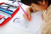 Schoolchild is drawing a man on his notebook with a pencil — Stock Photo